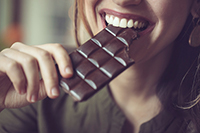 Image of a smiling woman eating dark chocolate.