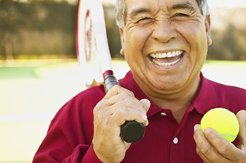 smiling man holding tennis equipment